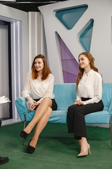 Female guests are sitting on sofa.journalist taking interview. morning show.