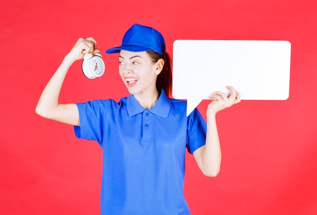 Female guide in blue uniform holding a white rectangular info board with an alarm clock .