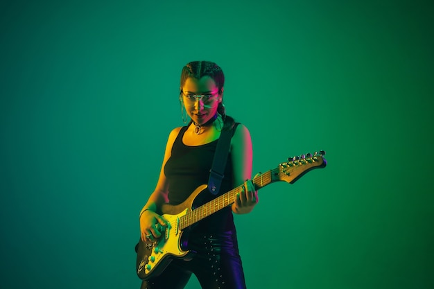 Female guitarist portrait isolated on green studio wall in neon light