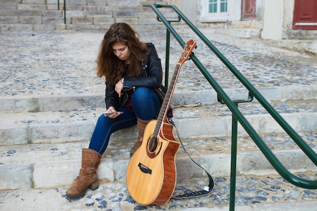 Female guitarist using smartphone on city stairs