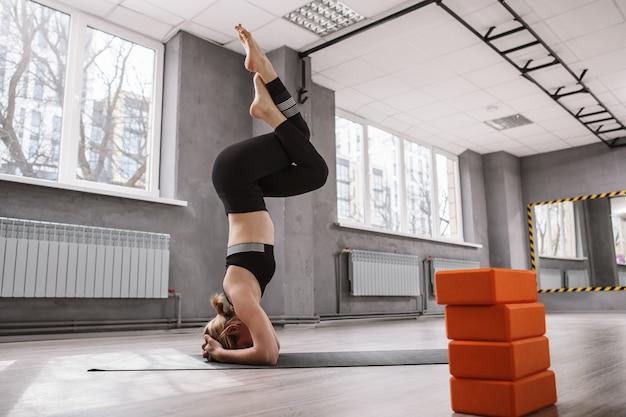 ヘッドスタンド アーサナのバランスをとる女性体操選手、スポーツ スタジオでのヨガの練習、前景のヨガ ブロック