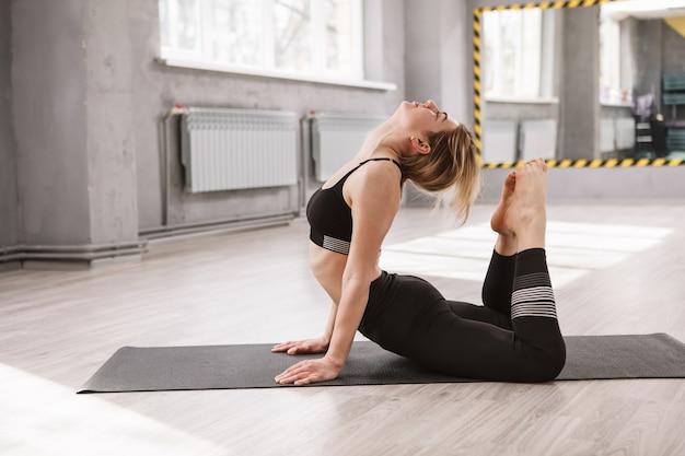 ヨガスタジオで運動し、背中を伸ばす女性体操選手