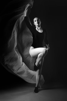 Female gymnast posing on black