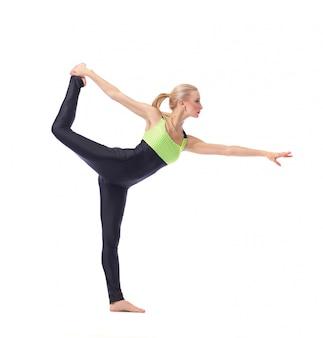 Female gymnast posing gracefully exercising on white