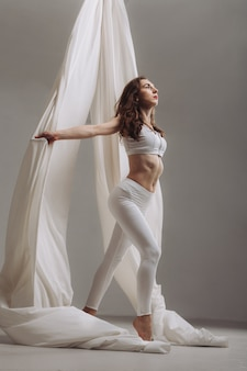 Female gymnast posing with aerial silk ribbons