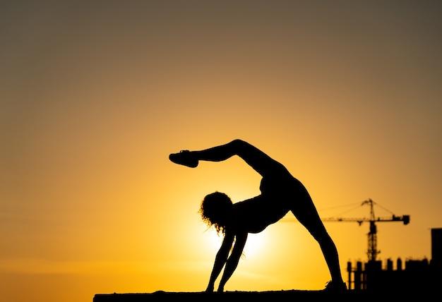 Гимнастка показывает свою гибкость и раскол во время заката на оранжевом небе с подъемным краном и концепцией свободы и счастья