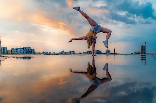Гимнастка стоит на одной руке и держит равновесие во время драматического заката с отражением в воде удивительных облаков