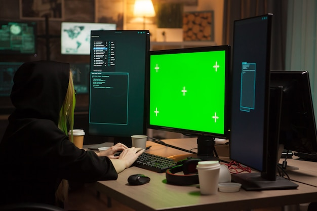 Женский хакер в толстовке с капюшоном перед компьютером с зеленым экраном.