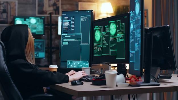 정부를 상대로 사이버 범죄를 저지르는 동안 얼굴을 가리기 위해 후드티를 입은 여성 해커.
