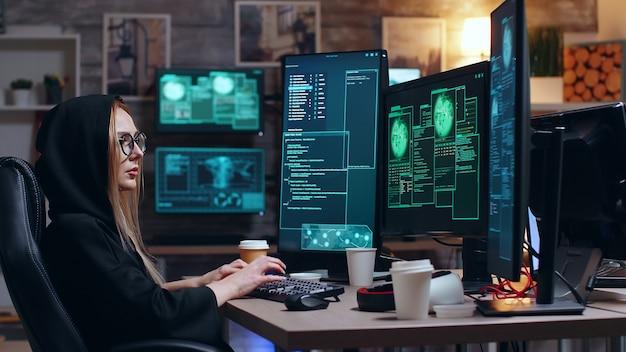 후드티를 입은 여성 해커가 위험한 바이러스를 사용하여 정부 데이터베이스를 취약하게 만듭니다.