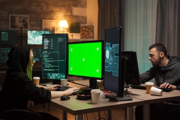 Женский хакер с капюшоном перед компьютером с зеленым экраном и преступником мужского пола.