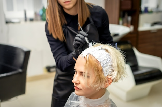 Female hair stylist applies white dye to hair of young female client in hair salon