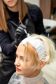 Женский парикмахер применяет белую краску к волосам молодой клиентки в парикмахерской
