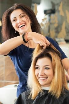 女性の美容師とクライアントがヘアカットを行うかどうかを決定します。健康な髪、最新のヘアファッショントレンド、ヘアカットスタイルのコンセプトの変化