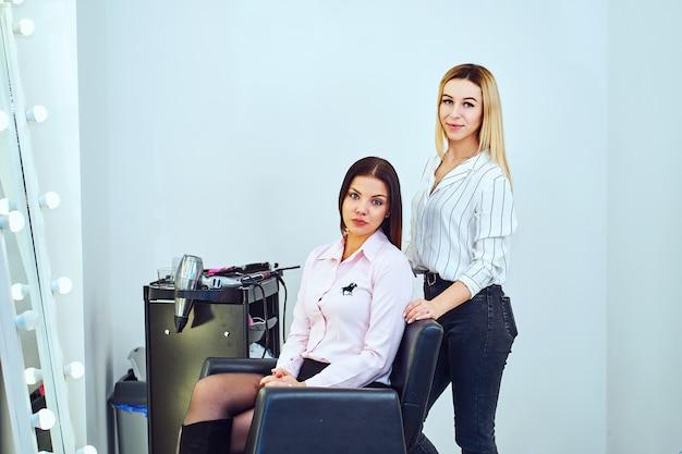 ストレートヘアアイロンを持っているサロンの女性美容師