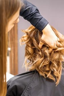 Женский парикмахер проверяет коричневую вьющуюся прическу молодой кавказской женщины в салоне красоты