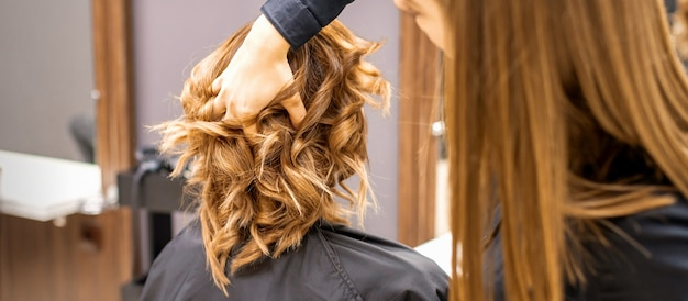Female hairdresser checks brown curly hairstyle of a young caucasian woman in beauty salon.