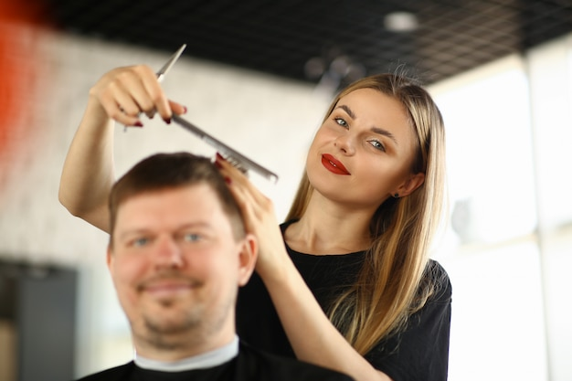 Female hairdresser combing male client in salon