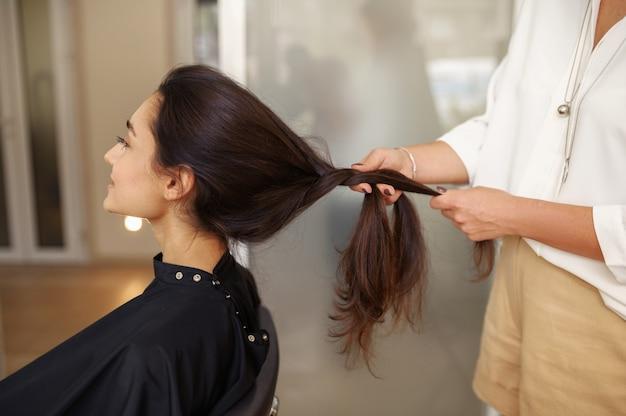 여성 미용사는 여자의 머리, 미용실을 빗질합니다. 헤어 살롱의 스타일리스트와 클라이언트. 뷰티 사업, 전문 서비스