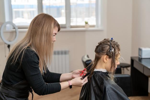 Женский парикмахер, стрижка волос молодой женщины