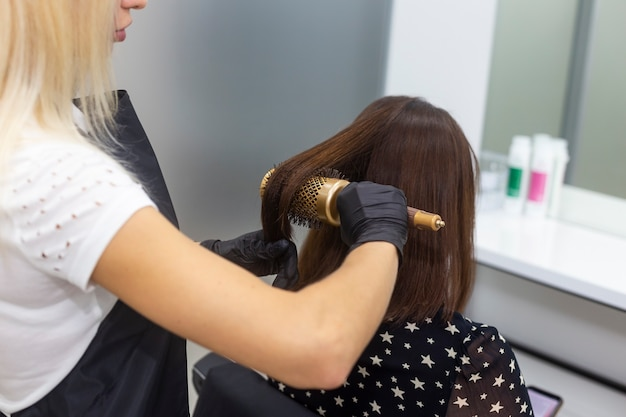 丸い櫛でヘアスタイリングをしている女性美容師。プロの美容ツール、機器。理髪サービス。ビューティーサロン、サービス。