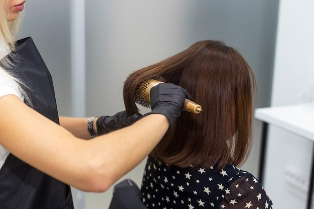 Female hairdresser doing hair styling with a round comb.