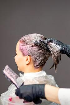 美容院で若い白人女性の髪を染める女性美容師