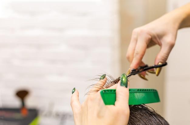Женские руки парикмахера делают стрижку для мужского клиента с помощью ножниц парикмахерских инструментов