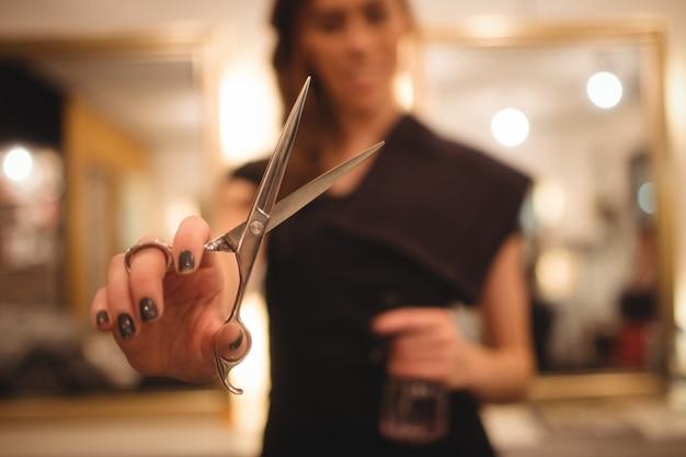 Женский парикмахер держит ножницы