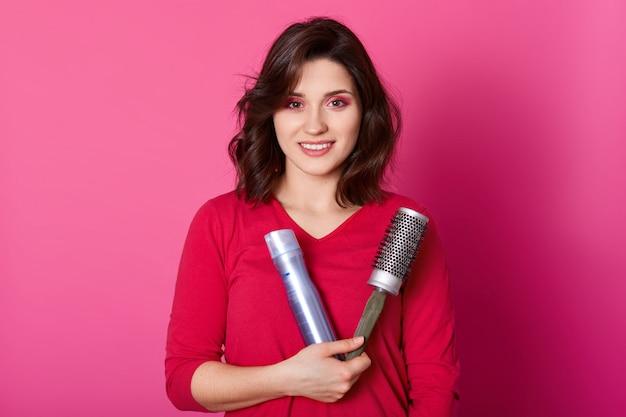 女性の美容師は櫛とヘアスプレーを保持し、赤いセーターを着て、ヘアスタイルを彼女のクライアントにする準備ができています