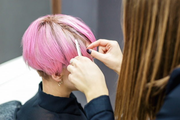 Female hairdresser is combing short pink hair of woman.