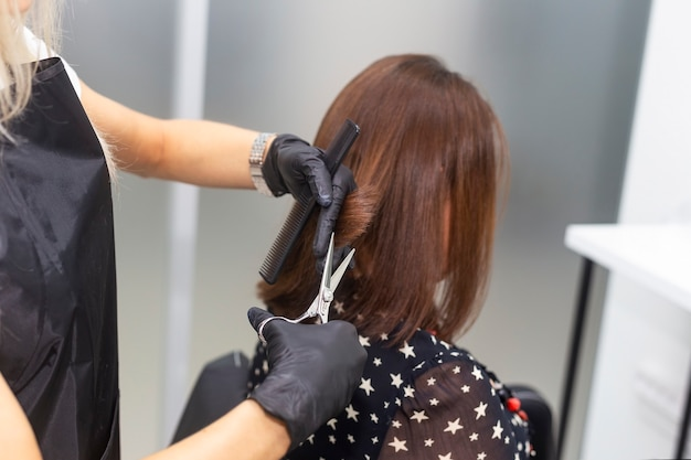Женский парикмахер делает стрижку. профессиональный парикмахерский инструмент, оборудование. парикмахерские услуги. салон красоты, сервис.
