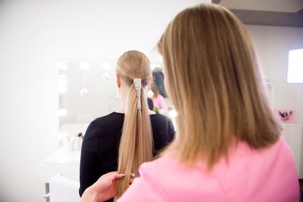 女性美容師が美容院で金髪の女の子にヘアスタイルを作ります。