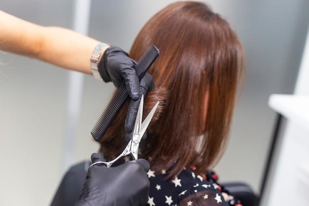 Female hairdresser makes a haircut.