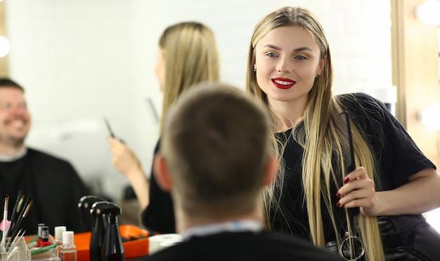 Женский парикмахер делает прическу для клиента мужчина