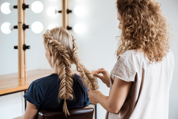 Female hairdresser making hairstyle to blonde woman in beauty salon