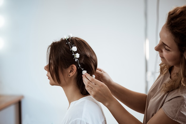 Female hairdresser making hairstyle to brunette woman in beauty salon