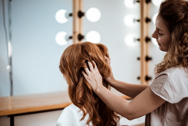 Female hairdresser making hairstyle to redhead woman in beauty salon