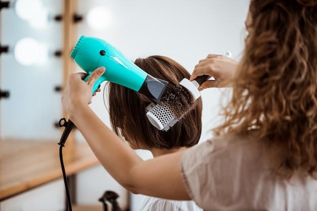 Женский парикмахер делает прическу для брюнетки в салоне красоты