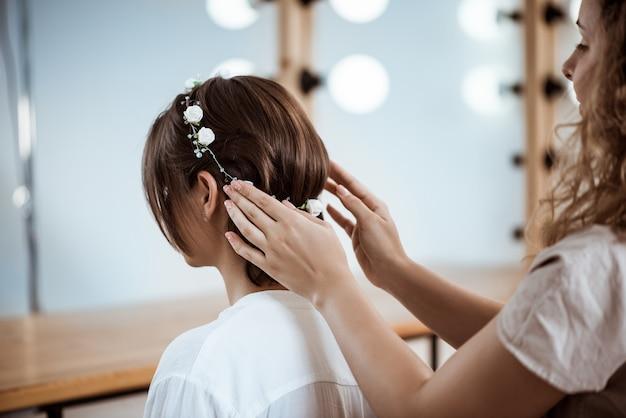 뷰티 살롱에서 갈색 머리 여자 헤어 스타일을 만드는 여성 미용사
