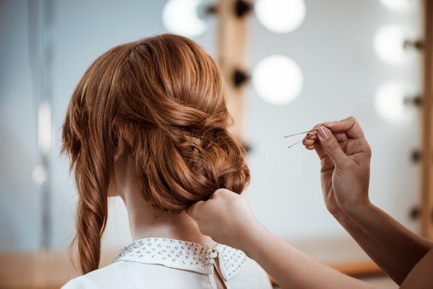 뷰티 살롱에서 빨간 머리 여자 헤어 스타일을 만드는 여성 미용사