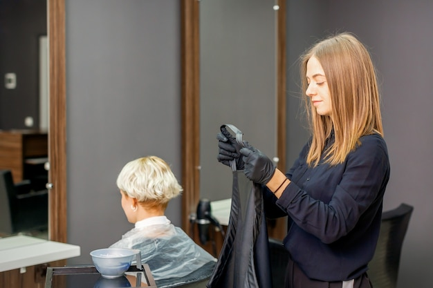 Female hairdresser prepare puts on black cape on the female client in a beauty salon