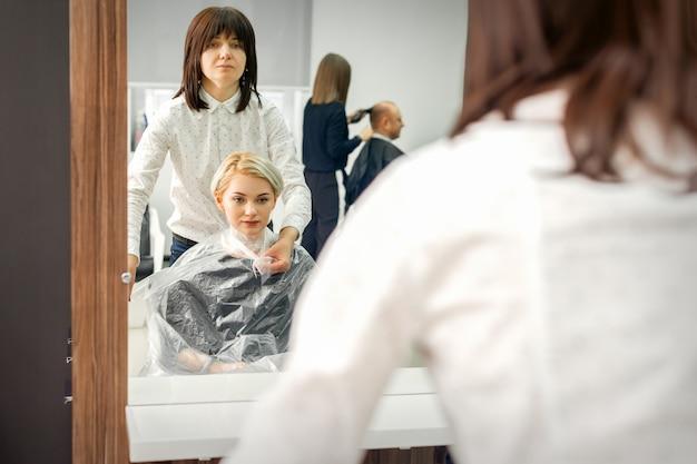 여성 고객에게 투명한 셀로판 케이프를 입은 여성 미용사