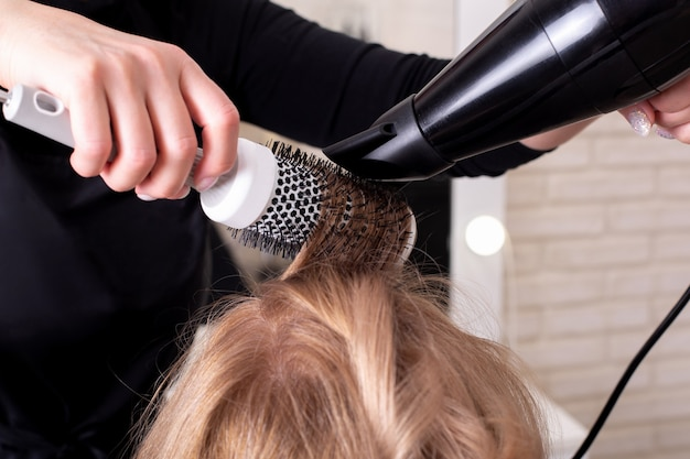 Female hairdresser's hand brushing and blow drying hair