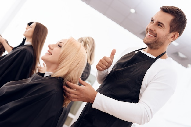Female hairdresser showing thumbs up to mature woman.