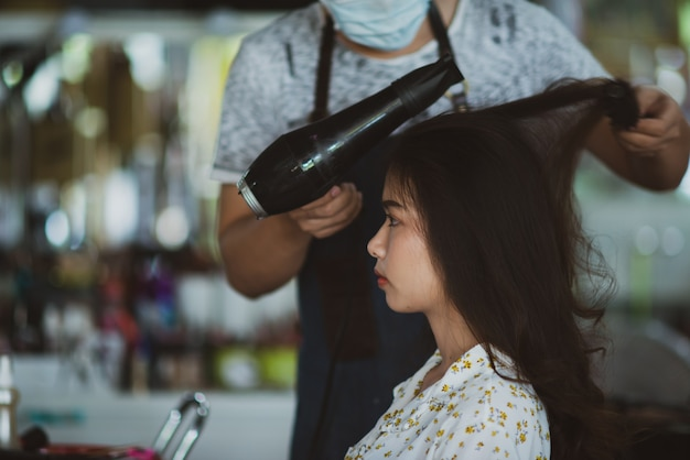 Female hairdresser standing, face makeup and making hairstyle to cute lovely young woman in beauty salon