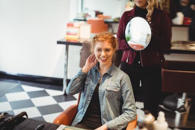 クライアントの髪をスタイリングする女性の美容師
