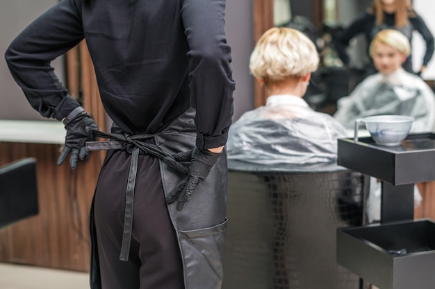 The female hairdresser ties up her apron