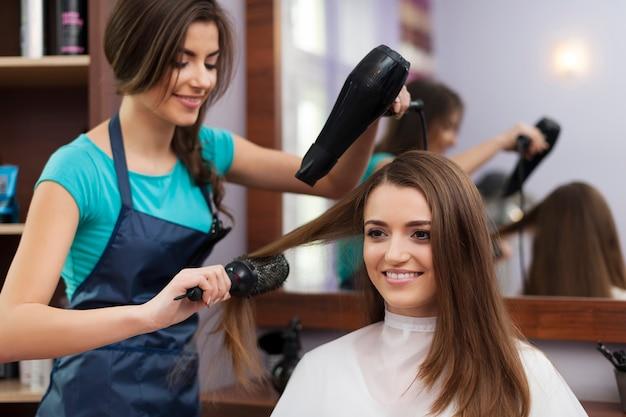 Женский парикмахер, используя расческу и фен