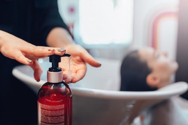 Женский парикмахер моет волосы клиента шампунем, парикмахерская. процесс создания прически в салоне красоты